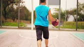 dunking : Back view of young man playing basketball: he is jumping up and throwing a ball to the basket successfully. Slowmotion shot