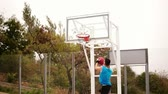 dunking : Tracking shot of a young man running with a ball and throwing a ball to the basket successfully. Basketball game. Slowmotion shot