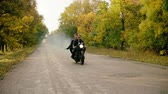 granada : Handsome man in sunglasses riding with his girlfriend on a motorcycle on the asphalt road in forest in autumn. His girlfriend is holding a smoke grenade. Slowmotion Vídeos