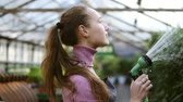 waterhose : Closeup view of young attractive female gardener in uniform watering plants with garden hose in greenhouse. Slowmotion shot