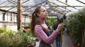 waterhose : Young attractive female gardener in uniform watering plants with garden hose in greenhouse. Slowmotion shot Stock Footage