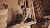 globale : Side view of a craftman working on a electric saw with wood. Pushes the wooden block by hands