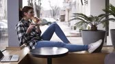 chillout : A brunette girl in a plaid shirt and jeans sits with outstretched legs by the window and enjoys her croissant. Smiling. Blurred street background Stock Footage