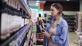 karar vermek : A woman in a supermarket in the alcohol department. Wine shelf. The girl chooses a bottle, holds a bottle of wine. Looks at prices