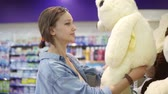 решать : Close up footage of the girl looking for the soft toys on the shelf in the supermarket. She is determined with a choice. Shelf with assortment of plush toys. Girl in casual clothes. Side view