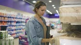 решать : A young girl in a denim shirt, chooses products in a hypermarket. Looks and touches the quality of the pillows or blankets on the shelf in the store. Blurred background
