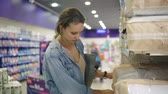 расходы : A beautiful woman chooses pillows or blanket in a supermarket. Determined with a choice. Take the packaging product from the shelf. Blurred background