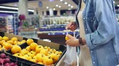 epicerie : Handheld footage of a girl selecting fresh yellow tomatos from the box in vegetable department. Grocery store. Girl adds tomatoes to the cellophane bag Vidéos Libres De Droits