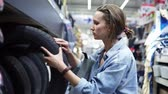 karar vermek : Cute girl in big shopping center selecting car tyres. Examination. Buyer. Rows of different car tyres. Side view