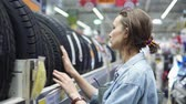 решать : Department of car accessories in the store. Large hypermarket. The girl is standing near the rack with the tires. Selects. Blurred store background