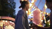 Young couple dating, meeting at the amusement park, male bring a cotton candy to her girlfriend. Kissing. Shine bright on the background. Low angle footage