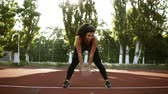 lunge : Slender sexy athlete performs slopes down in black legging. Exercises to strengthen the muscles of the hips and legs. Small outdoors stadium