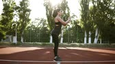 lunge : Young woman athlete in sports clothes squat exercise outdoor. Spectacular brunette in black T-shirt and legging enthusiastically doing beloved physical exercise. Side view