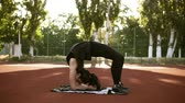 lunge : Fitness woman doing bridge pose yoga exercise. From standing pose to bridge position. Working out outdoors on the fitness stadium Stock Footage