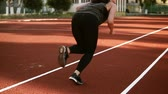 lunge : Athlete woman starting running on running track. Sporty brunette woman in black leggings jogging by the trackline on the outdoor stadium. Backside view