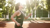 lunge : Gorgeous scene of a beautiful caucasianwoman slowly jogging outdoors on the stadium. Slow motion side view of a long haired female runner. Sun shines on the background, green trees Stock Footage