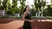 lunge : Portrait of young woman, who is warming up her hand muscules before training, slow motion. Beautiful brunette lady in black sportswear is standing on outdoors small stadium Stock Footage