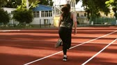 lunge : Slow motion footage of a female runner starting to run on the track line on the small outdoors stadium. Fit girl in black leggings working out outdoors