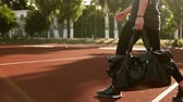 tragetasche : Young pretty fitness woman carrying sports bag while walking by outdoors stadium. No face. Sun shines on the background Stock Footage