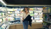 mercearia : At the supermarket: happy young woman dances through goods and dairy products on the shelves. Take off her black jacket, having fun Stock Footage