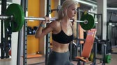traseiro : Charming young girl in sport clothes - bra and leggings doing sit-ups with barbell during workout in the gym, breathing
