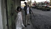 zombi : Portrait of creepy male and female ghost or zombie walking with wounded face and bloody clothes. Man holding saw and woman is with a stick. Industrial, abandoned town and tracks on the background