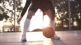 basse cour : Young girl basketball player exercising on outdoor court. Bouncing the ball low at the ankle level, practicing. Sun shines on the background Vidéos Libres De Droits