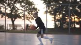 дриблинг : Handhelded footage of a young girl basketball player training and exercising outdoors on the local court. Dribbling with the ball, bouncing and make a shot