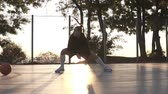 drible : Caucasian young sporty woman in hoodie and shorts warming up in morning on basketball court. Stretching her legs before basketball training. Sun shines on the background Stock Footage