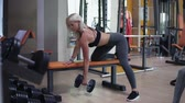 dumbell : Blonde woman working out with a dumbbell weight at a modern gym with a variety of equipment leaning forward over a bench as she exercises her arm Stock Footage