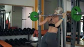 bunda : Young attractive blonde girl sit ups with barbell. Female successfully practices workout and crossfit training at gym