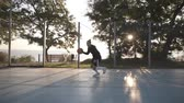 abroncs : Side footage of a young girl basketball player training and exercising outdoors on the local court. Dribbling with the ball, bouncing and make a shot