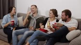 enjoying : Friends are gathering together and having fun at the living room with loft interior. Male and female company, The girl with a big red bowl with popcorn, everyone drinking beer or soda, laughing, talking