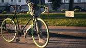 舗装された : Close up footage of woman in sneakers walking besides a bicycle in the morning park or street. Side view of a young woman walking with her trekking bike, holding a dry leaf in hand