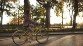 舗装された : Pretty little girl riding yellow coloured bike on the street in summer city park. Trees and sunshines on the background