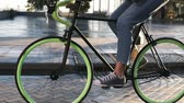 bisiklete binme : Close up footage of female feet cycling a bicycle in the morning by paved city street with wet asphslt . Side view of a young woman riding a trekking bike with green wheels, wearing sneakers and jeans Stok Video