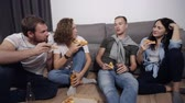 feestzaal : Food, leisure and happiness concept - four smiling young people eating pizza at home and drinking a beer while sitting on the floor. Front view