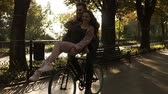 ruder : Loving young couple have fun riding on the same bike in outdoor activity with sun backlight on the background. Girl is sitting on the rudder and kissing her boyfriend Stock Footage