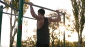 тянуть : Fit muscular man in black shirt doing pull-ups on horizon bar on sports ground with trees and sun shines on the background. Slow motion