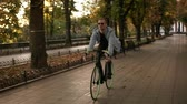 舗装された : Front footage of a young smiling man in sunglasses cycling a bicycle in the morning park or boulevard. Slow motion of young man riding a trekking bike. Summer, autumn empty city park 動画素材