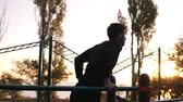 párhuzamos : Fit man doing triceps dips on parallel bars at park exercising outdoors in the morning while listening to the music in earphones