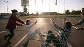 courses : Young millennials people racing with shopping carts - Happy crazy friends having fun with trolleys in car park. Girls in the corts giving each other high five. Youth lifestyle, friendship and party concept. Sun shines on the background