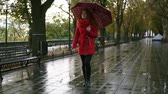 bulvár : Full legth of female person in red walk under rain with umbrella. Red haired woman wearing red coat with umbrella walking through city park. Front view