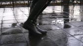 footing : Woman take walk at autumn park walking along the pavement alley. Close up legs and shoes view. Graceful lady wear black high boots. Autumn weather, rayny, wet road. Side view