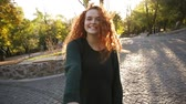 vést : Young attractive girl in dark knitted sweater joyfully walking in a colorful autumn city park on pavement. Red curly haired girl enjoying autumn foliage, turns around joyfully smiling at camera, leading her boyfriend with hand. Rare view