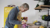 adornar : Professional confectioner woman decorates cake with flowers on white modern kitchen studio. Shorthair female chef makes a wedding or birthday cake with fresh, eatable flowers. Footage from the side