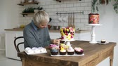 adornar : Confectionary. Chef decorates an order for a holiday. Woman with grey colored hair decorates cake with little flowers to order. Muffins on a wooden table on foreground