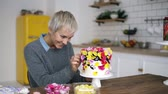 adornar : Smiling woman in grey sweater decorates cake with flowers on white modern kitchen studio. Shorthair female chef makes a wedding or birthday cake with fresh, eatable flowers, choosing best flowers for cake