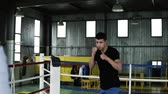 uppercut : Motivated, young boxer in casual is training with coach on the ring. View from the back of the coach holding a heavy ball while guy is practicing punches and tactics steps. Old style gym on the background
