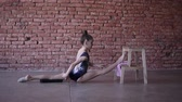 banquinho : Young fit teenage girl warming up stretching in a studio in front the brick wall. Leg split lying fore leg on a wooden stool